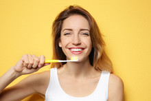 Portrait Of Young Woman With Toothbrush On Color Background