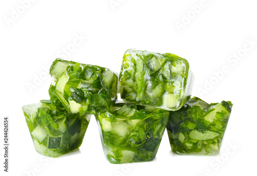 Ice cubes with cucumber slices and herbs on white background