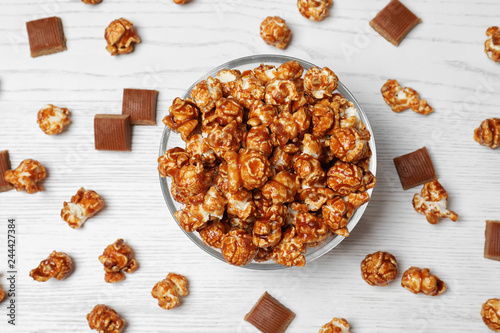 Flat lay composition with caramel popcorn on white wooden background