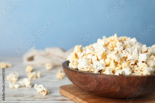 Wooden bowl with tasty popcorn on table. Space for text