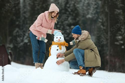 Fotografie, Tablou Couple making snowman outdoors. Winter vacation