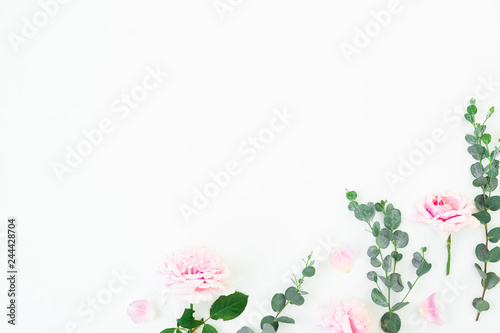 Fotobehang Bloemen Pink rose flowers and eucalyptus branches on white background. Flat lay, top view. Valentines day