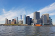 View of the island from the Hudson River on the port with moored ships and skyscrapers on the horizon. Office buildings from the river in New York