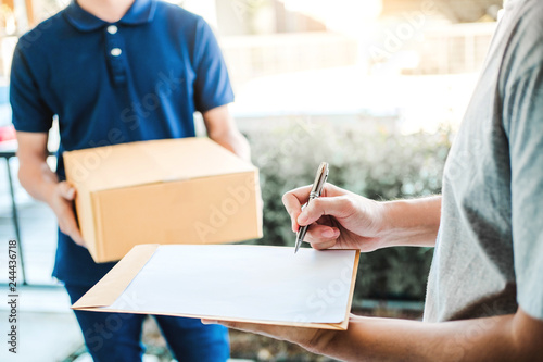Foto  Customer Man signature in clipboard to receive package from professional deliver