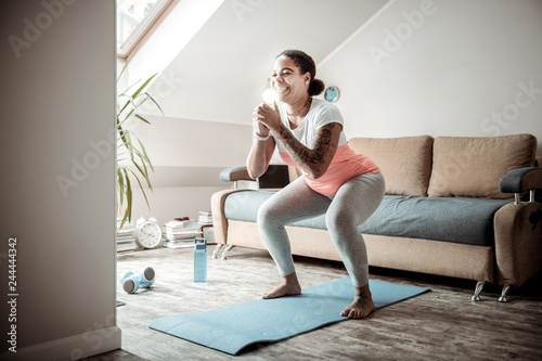 Fotografia Smiling curvy lady doing wide squats while getting in order