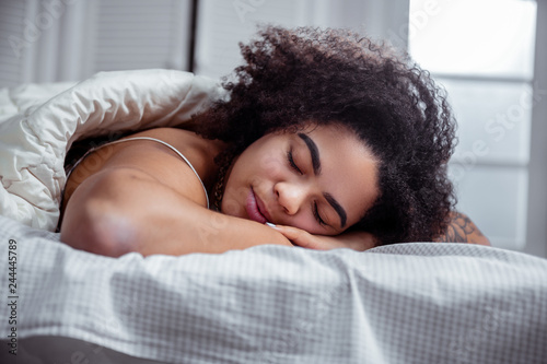 Fotografía  Peaceful dark-skinned woman resting on bed and having nice sleep