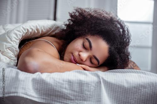 Fotografie, Obraz  Peaceful dark-skinned woman resting on bed and having nice sleep