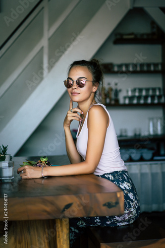 Fototapety, obrazy: A beautiful woman has breakfast in a stylish cafe, a healthy breakfast, fruit, freshly squeezed juice, tropical location.