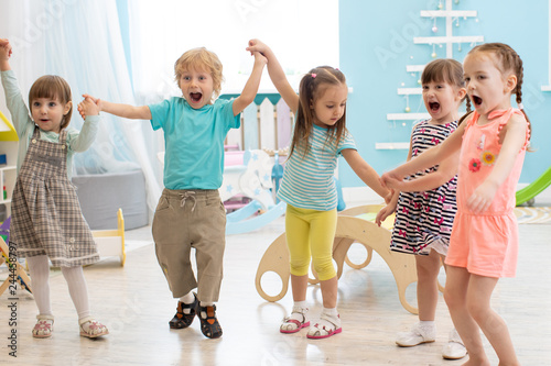 Group of happy kindergarten children jumping raising hands while having fun in entertainment center