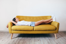 Happy Young Woman Relaxing On Couch At Home
