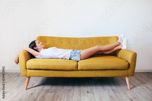 Deurstickers Ontspanning Happy young woman relaxing on couch at home