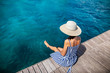 canvas print picture - Happy woman in hat relaxing on sea pier in Sardinia island, Italy