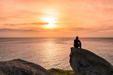 Man Sitting On Big Rock With Sightseeing At Sunset