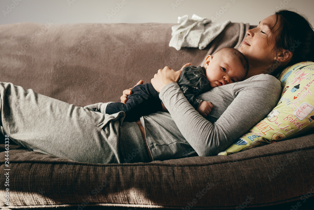 Fototapeta Mother sleeping on a couch with her baby on her