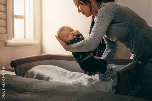 Mother putting her baby to sleep on a bedside baby crib Canvas Print