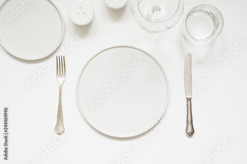 Festive modern white table setting. Plates and cutlery on white. View from above.