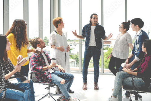 Fotografia  Attractive young multiethnic group talking at relax zone in coffee break time at office