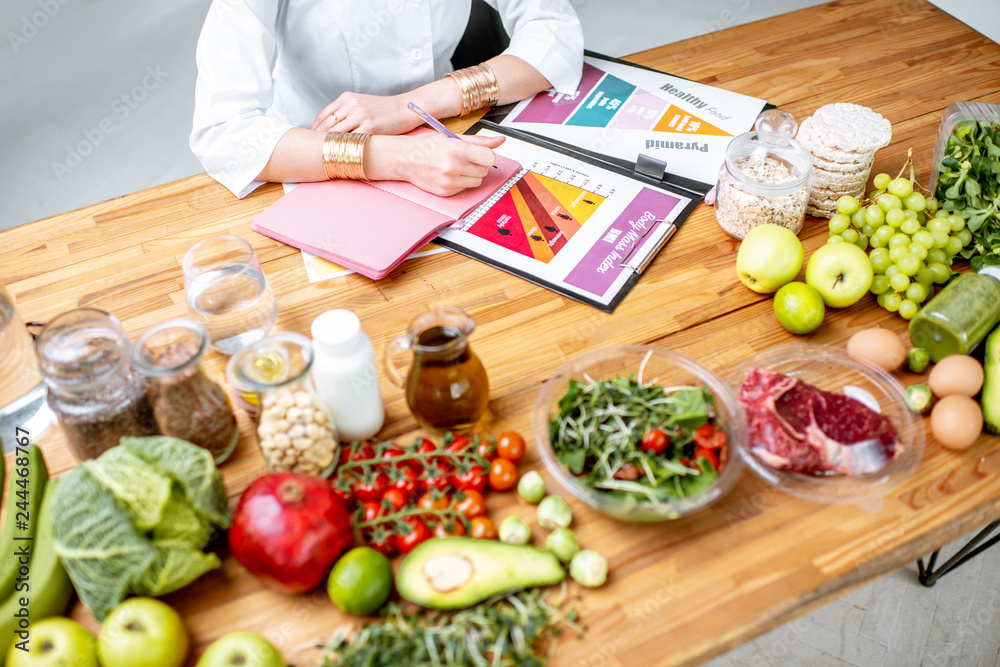 Fototapety, obrazy: Dietitian writing diet plan, view from above on the table with different healthy products and drawings on the topic of healthy eating