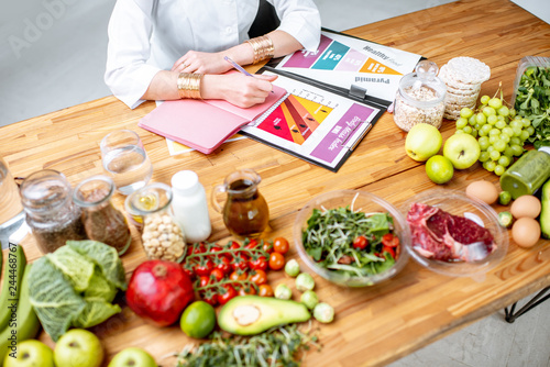 Fototapeta Dietitian writing diet plan, view from above on the table with different healthy products and drawings on the topic of healthy eating obraz