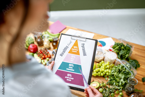 Fotografía  Holding schematic meal plan for diet with various healthy products on the backgr