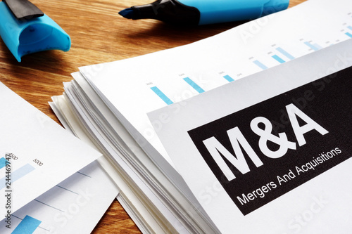 Photo Documents about mergers and acquisitions m&a with a pen.