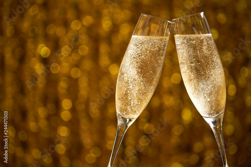 Fotografía  Glasses of champagne on a golden background, party or holiday concept
