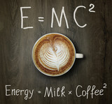 The cup of black coffee with milk and two funny formulas. Wooden background.