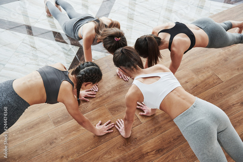 Fotobehang School de yoga Young girls doing push ups together. Head near head pose on the wooden and tile floor