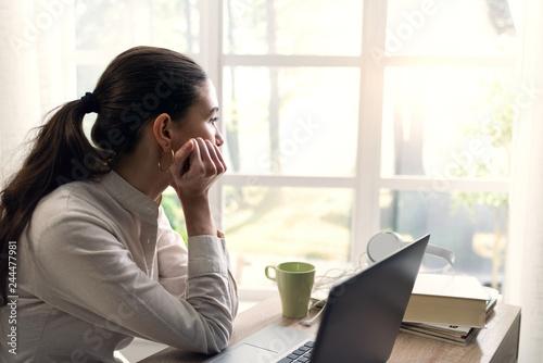 Fotografía Pensive young woman at home looking away