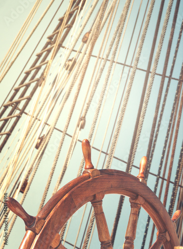 Foto auf AluDibond Schiff Skipper's wheel and sea tackles on the mast on a tall ship. Rigging ropes at blur background on a sailing vessel for your concept in marine style.
