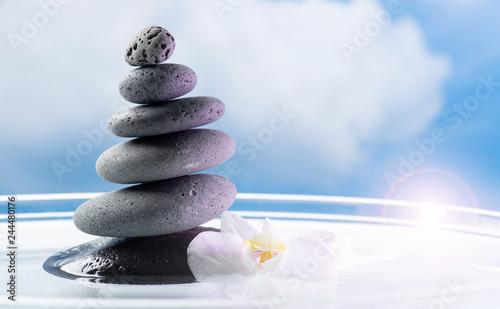 Photo Stands Orchid Steinturm mit Orchidee Blüte im Wasser stehend vor weißblauem Himmel