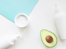 Skincare Still Life In Flat Lay Different Cosmetic Products In White Bottles, Jars And A Half Of Avocado Are Lying On Two Tone Background Template For Posters And Banners