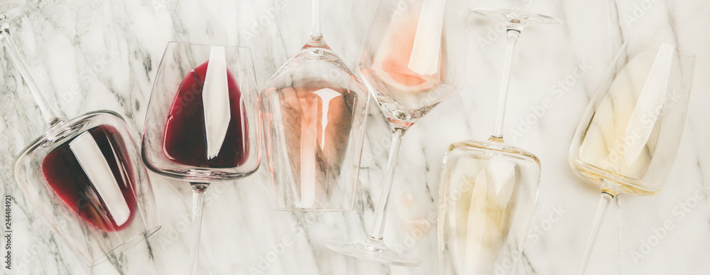 Fototapeta Flat-lay of red, rose and white wine in glasses and corkscrews over grey marble background, top view, wide composition. Wine bar, winery, wine degustation concept