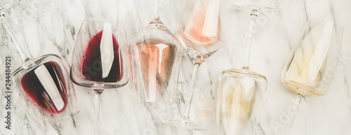 Flat-lay of red, rose and white wine in glasses and corkscrews over grey marble background, top view, wide composition. Wine bar, winery, wine degustation concept