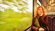 Junge Rothaarige Schöne Sexy Frau Sitzt Nachdenklich Tagträumend In Einer Fahrenden S-Bahn Die Bäume Am Fenster Rasen Vorbei Mit Textfreiraum