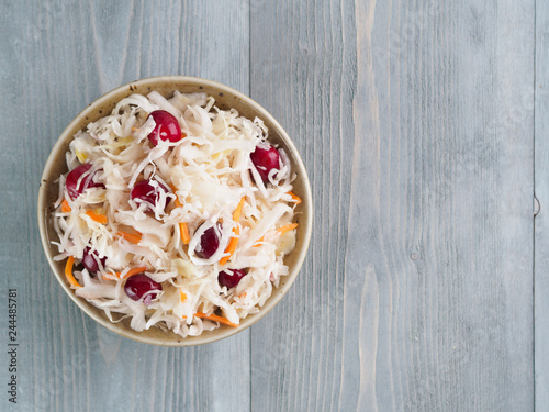 Traditional russian appetizer sauerkraut with cranberry and carrot in craft plate on gray rustic wooden table Canvas Print