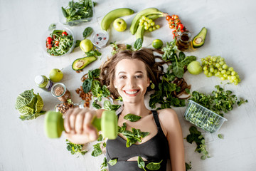 Beauty portrait of a sports woman surrounded by various healthy food lying on the floor. Healthy eating and sports lifestyle concept