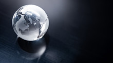 World Globe Crystal Glass Reflect On Black Glossy Table. Global Business And Economy. Environmental Conservation Or Ecology Concept