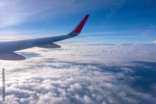 Türaufkleber Flugzeug The wings of the plane flying over the white clouds in the daytime