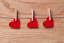 Red Hearts On Clothespins On Wooden Background