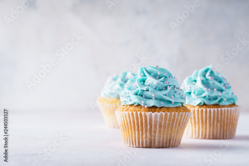 Платно Vanilla cupcakes with blue frosting decorated with sprinkles.