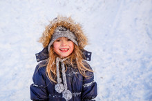 Cute Little Girl Wearing Navy Jacket And Knitted Hat Playing With Snow In Winter Park. Child Walking In Snowy Forest. Family Vacation With Kid In Mountains