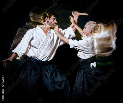 two budokas fighters man and woman practicing Aikido studio shot isolated on bla Wallpaper Mural