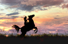Сowgirl Riding Rearing Stallion Standing Hind Legs On Horizon Line. Atmospheric Sunset With Female And Horse Silhouette Before Storm On сolorful, Cloudy Stormy Sky Background.