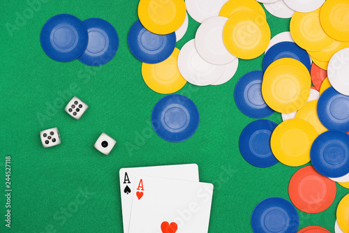 Photo top view of green poker table with multicolored chips, dices and two unfolded as