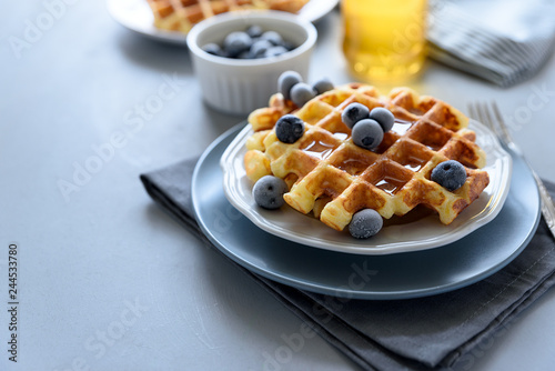 Fotografía  Belgian waffles with blueberries and honey on gray wooden background
