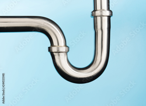 Leinwand Poster Stainless steel sink pipe on isolated on light blue background