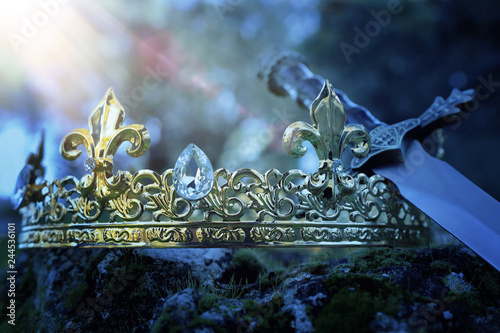 mysterious and magical photo of silver king crown and sword over the stone covered with moss in the England woods or field landscape with light flare. Medieval period concept.
