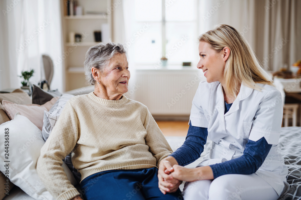Fototapeta A health visitor talking to a sick senior woman sitting on bed at home.