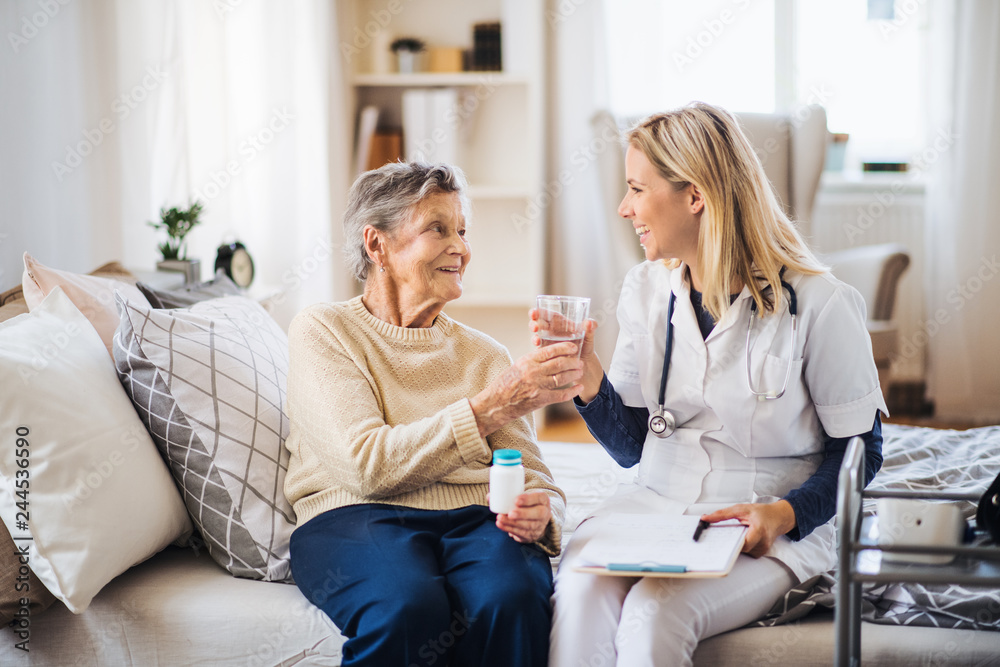 Fototapety, obrazy: A health visitor giving a senior woman a glass of water to take pills.